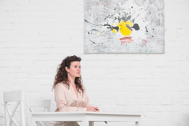 ダイニングテーブルに座っている若い女性の側面図