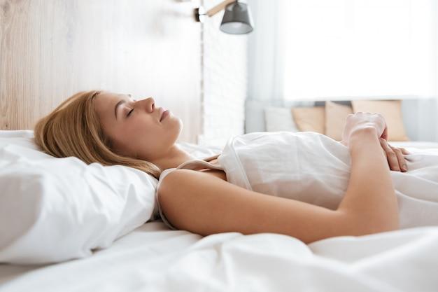 ベッドで寝ている若い女性の側面図