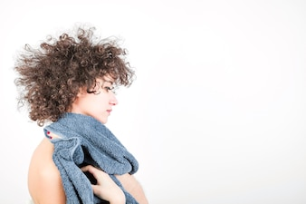 Side view of young woman with curly hair wipes her body with towel against white background