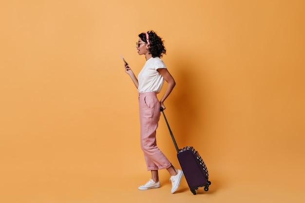 Вид сбоку молодой женщины с чемоданом