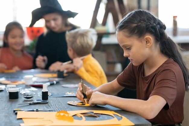ハロウィーンのポストカードを準備する油絵の具を持つ少女の側面図