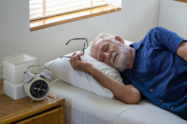 Side view of old man sleeping on bed