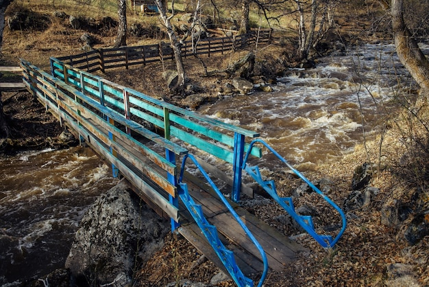 Side view old wooden bridge with peeling blue paint, over a stormy mountain stream. meltwater in the river running down the mountains. early spring.