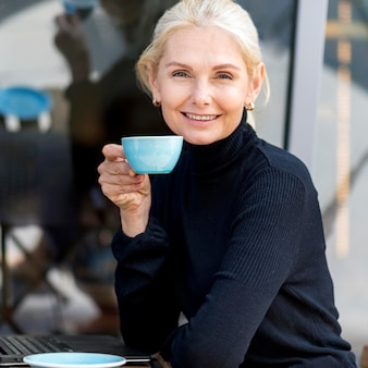 Side view of older business woman enjoying coffee outdoors while working