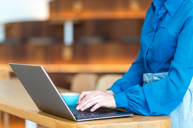 Side view of older business woman working on laptop