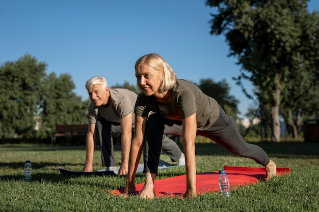 Side view of older couple practicing yoga outdoors