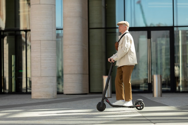Side view of older man in the city riding an electric scooter