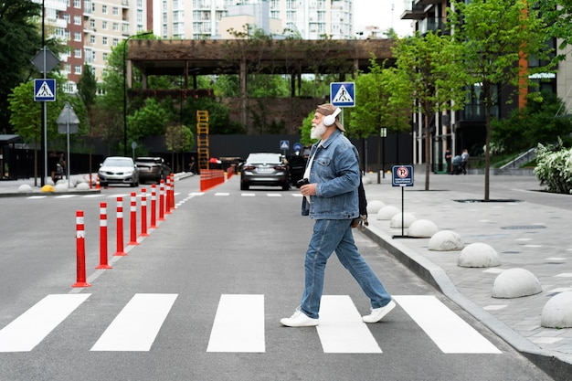 Side view of older man crossing the street while listening to music on headphones