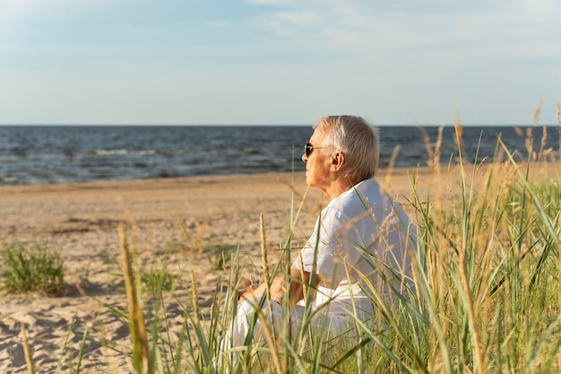 Side view of older man enjoying his time by the beach