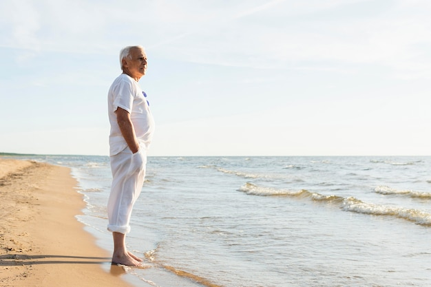 Side view of older man enjoying the view at the beach