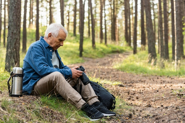 Side view of older man holding camera while resting in nature