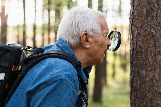 Side view of older man in nature with magnifying glass