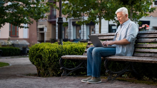 Side view of older man outdoors on bench with laptop