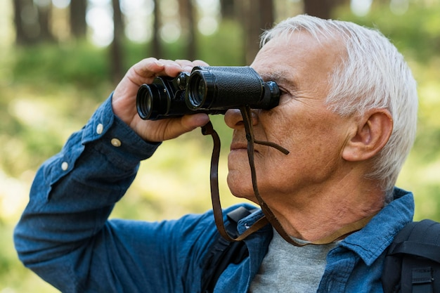 Side view of older man outdoors with binoculars