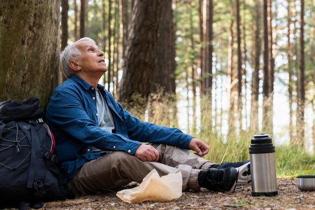 Vista laterale dell'uomo più anziano che riposa mentre viaggia all'aperto