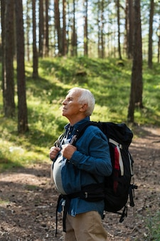 Side view of older man traveling with backpack in nature