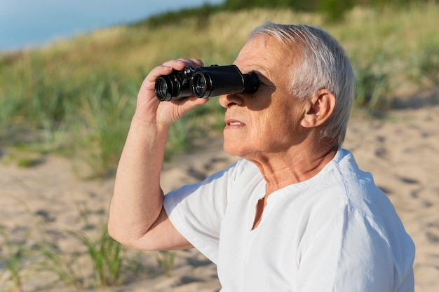 Side view of older man with binoculars outdoors