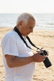 Vista laterale dell'uomo più anziano con la macchina fotografica sulla spiaggia