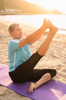 Side view of older woman doing yoga on the beach