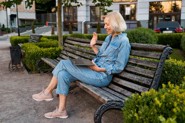 Side view of older woman outdoors on bench waving at laptop