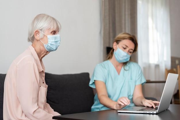 Vista laterale della donna anziana con infermiera femminile e laptop