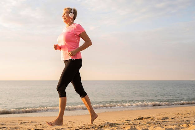 Side view of older woman with headphones jogging on the beach