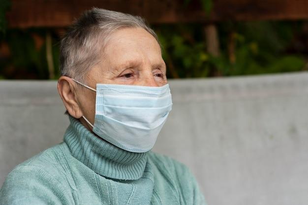 Vista laterale della donna anziana con maschera medica e copia spazio