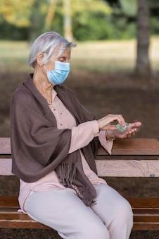 Vista laterale della donna anziana con maschera medica e disinfettante per le mani