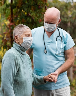 Vista laterale della donna anziana con maschera medica e infermiere maschio