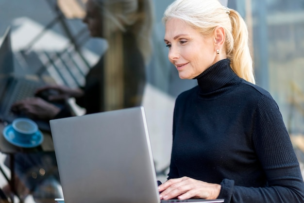 Side view of older woman working on laptop outdoors while enjoying coffee