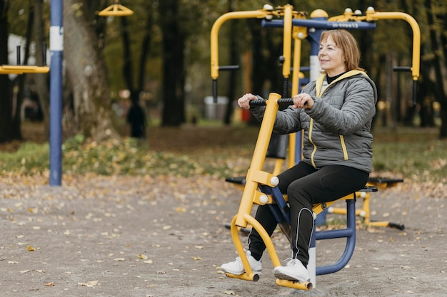 Side view of older woman working out outdoors with copy space