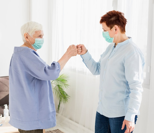 Side view of older women bumping fists while wearing medical masks