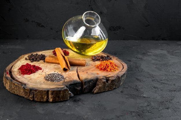 Вид сбоку оливковое масло в кувшине со специями на тарелке с корицей