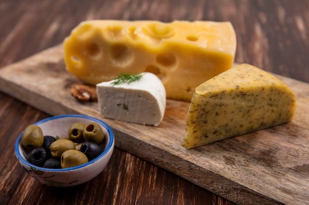 木製の背景の上のスタンドにチーズの品種とオリーブの側面図