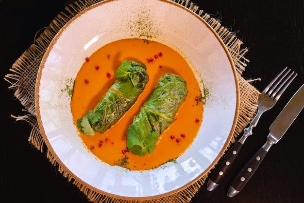 東欧料理の側面図、サワークリームとニンジンを添えた肉または野菜を詰めたロールキャベツの葉。上面図