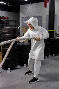 スポーツのヒジャーブを身に着けて、バトルロープでクロスフィットトレーニングをしているアラビアの女性アスリートの側面図。定期的なスポーツは免疫システムを高め、健康を促進します。健康的な生活様式