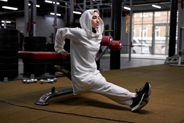 강렬한 훈련을받은 아랍 여성의 측면보기, 스포츠 장비에 몸을 기울이고 몸을 들어 올리고 쪼그리고 앉는 모습. hijab에서 이슬람 여자 혼자 운동을