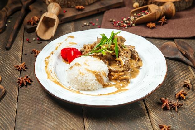 Вид сбоку на бефстроганов с рисом на деревянном столе