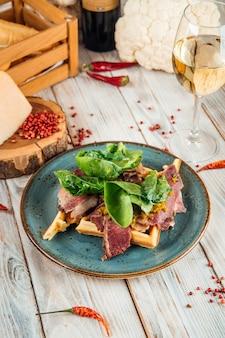 木製のテーブルに牛肉のパストラミと緑とベルギーワッフルの側面図