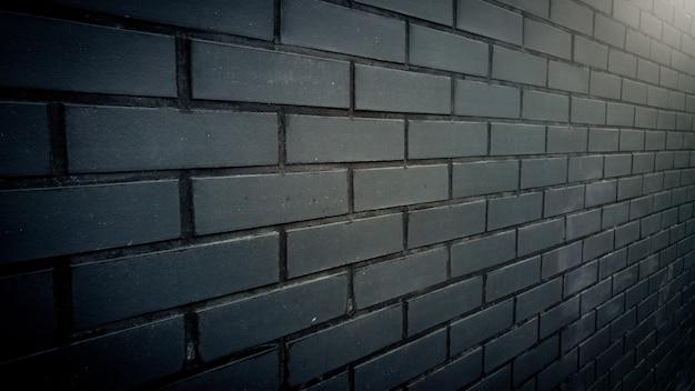 가로등에 의해 점화하는 검은 벽돌 벽에 측면보기