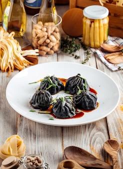 Вид сбоку на китайские черные пельмени с соевым соусом