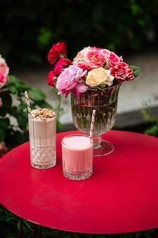 Вид сбоку на шоколадные и клубничные молочные коктейли на красном столе