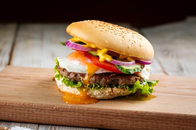 Вид сбоку на классический бургер с яйцом на деревянной доске