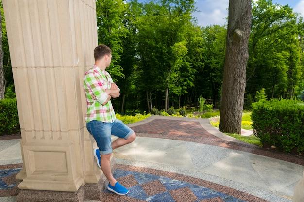 공원이나 마당에 있는 나무를 마주한 바깥 돌담 근처에 서 있는 명상적인 젊은 성인 남자의 측면