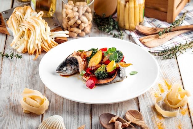 白い皿に野菜でいっぱい調理されたスズキの魚の側面図
