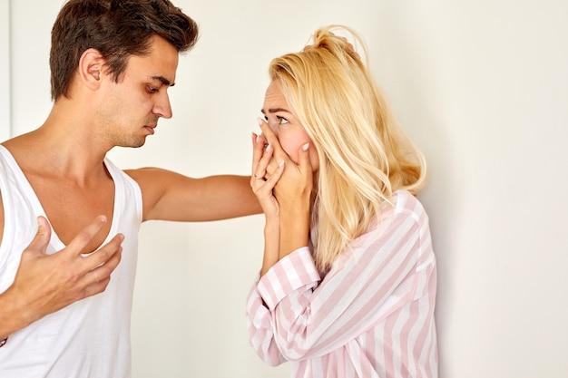 Вид сбоку на жестокий мужчина, ругающий жену дома в светлой комнате, семейный конфликт и оскорбительные токсичные отношения