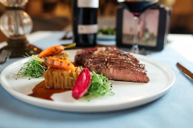 Вид сбоку на нарезанный стейк рибай из говядины с картофелем на белой тарелке