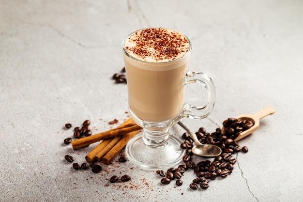 콘크리트 배경에 유리 머그잔에 카카오로 장식 된 커피 라떼의 측면보기