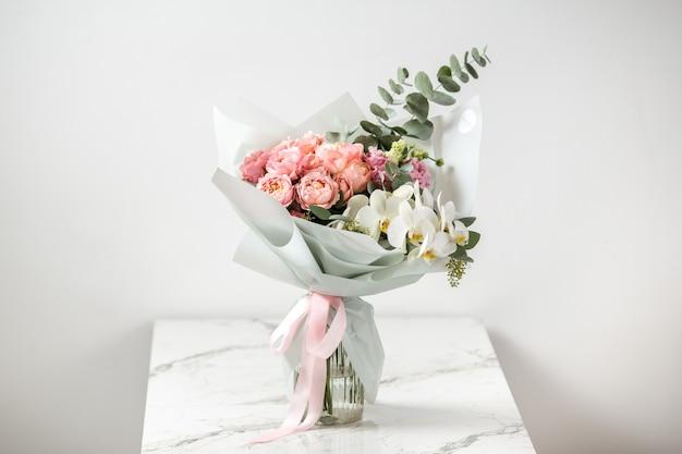 Вид сбоку на нежный букет розовых роз на белой поверхности