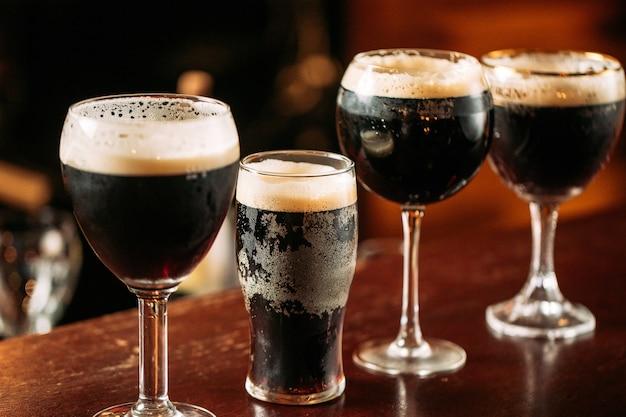 Вид сбоку на разные бокалы с темным разливным пивом на столе в баре